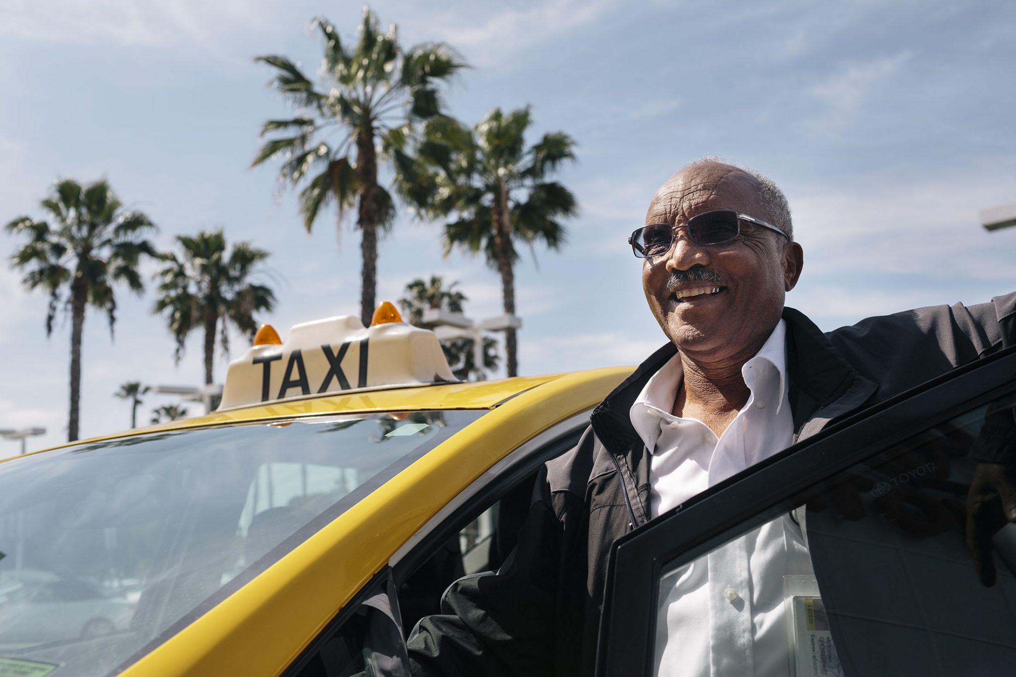 Mesghina Ghebrehiwat, 70, who goes by the name Alex, is the owner of Friendly Cab in San Diego. Ghebrehiwat, originally from Eritrea, has been driving at taxi in San Diego for 14 years and was an early adopter of switching to a hybrid vehicle in 2012 because of incentives offered by Mossy Toyota. Mossy offered the San Diego taxi drivers zero down and low or no interest financing, driver discounts, free carwashes and preferred service if they would switch to driving a Prius.