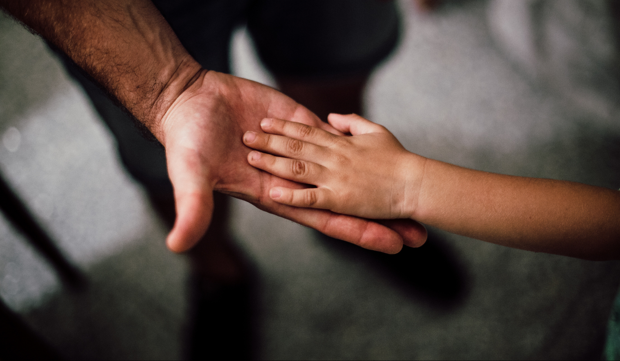 Father holding son's hand